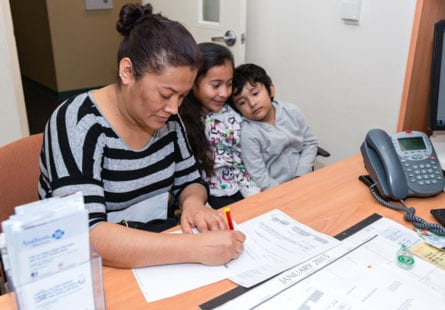 Guadalupe Carrera, 36, with her daughter Eva Maqueda, 9, and son Jose Maqueda, 5, fills out an application for health insurance assistance at El Proyecto Del Barrio Family Health Care Clinic on Thursday January 8, 2015 (Photo by Heidi de Marco/KHN).